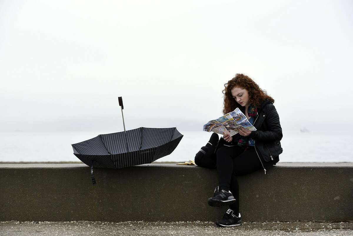 Caoimhe Burke, visiting from Dublin, Ireland, looks at her map during a break in the rain at Crissy Field in San Francisco, CA, on Thursday, December 8, 2016.