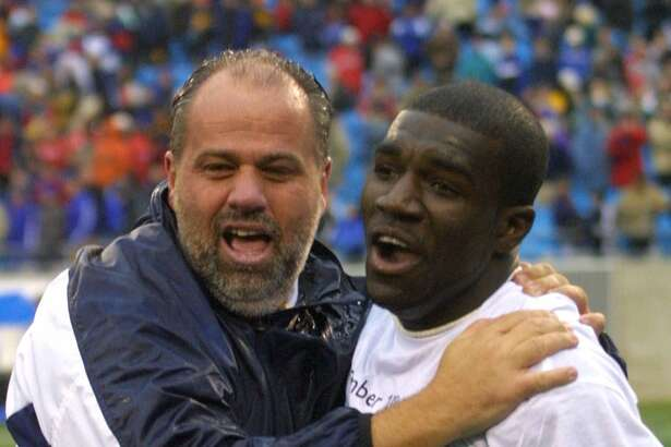 Connecticut coach Ray Reid celebrates with Chris Gbandi after Connecticut defeated Creighton 2-0 in the NCAA men's Division I championship Sunday, Dec. 10, 2000, at Ericsson Stadium in Charlotte, N.C. It was Connecticut's first NCAA men's soccer title since 1981.