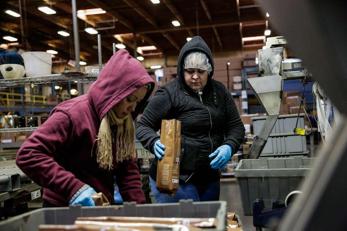 Margarita Salgado and Alba Balladares (right) package freshly ground batches of coffee at Peet's Roastery in Alameda, California, on Thursday, Dec. 8, 2016.