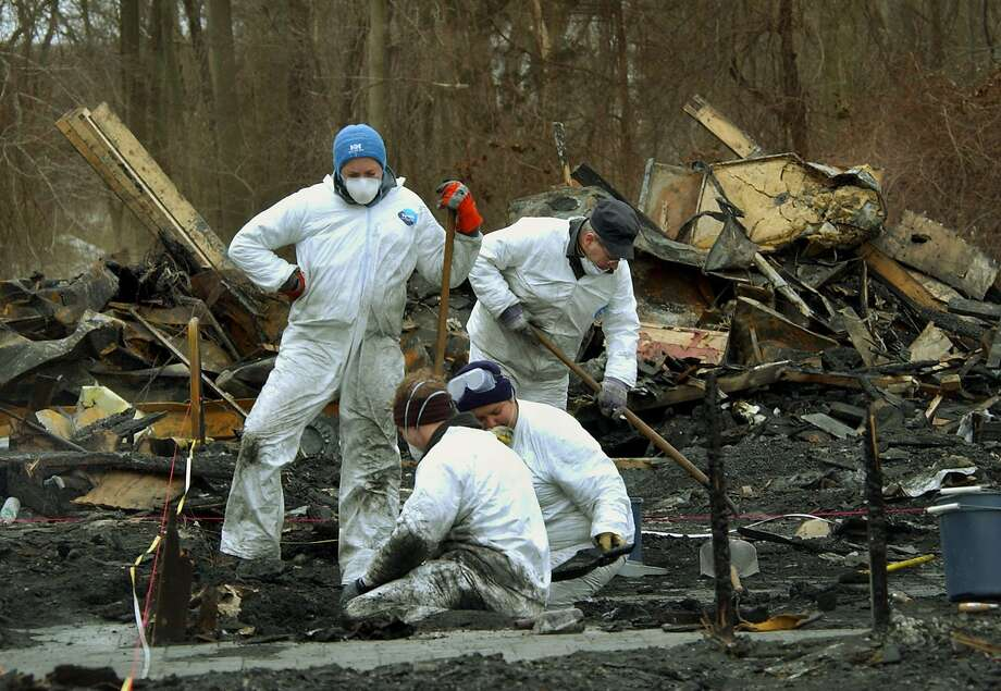FILE - In this Friday, Feb. 28, 2003, file photo investigators continue to sift through the charred wreckage of The Station nightclub in West Warwick, R.I., after a deadly fire eight days earlier. Relatives of those killed in a 2003 nightclub fire that claimed 100 lives in Rhode Island said they see troubling parallels with the warehouse party fire in Oakland, Calif. As a criminal investigation unfolds, they're warning of a long legal road ahead. (AP Photo/Elise Amendola, File) Photo: Elise Amendola, Associated Press