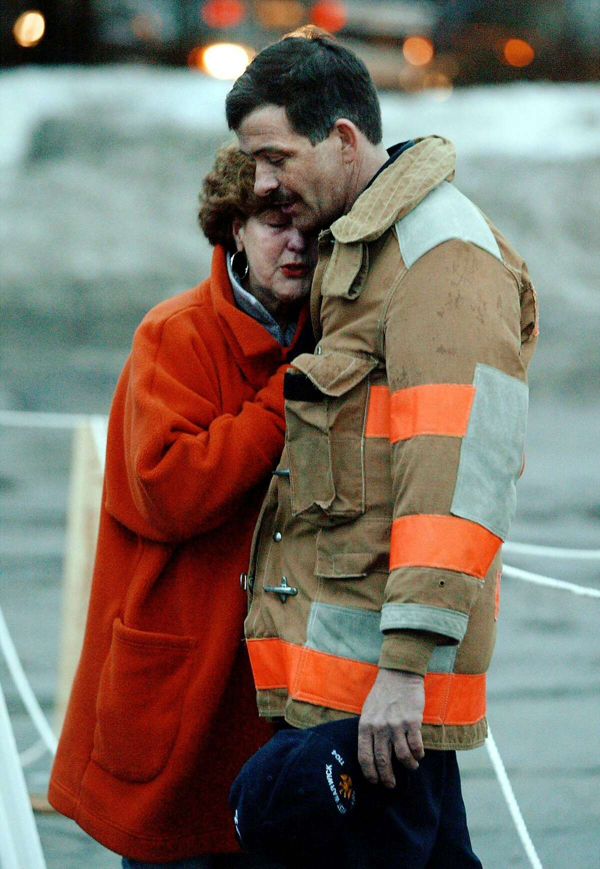 """Sharon Rayche (L) hugs West Warwick Fire Department Battalion Chief Wayne Willette at the site of the deadly February 21 fire at """"The Station"""" night club in Warwick, Rhode Island, February 23, 2003. The fire, which killed at least 96 people and injured at least 187, is believed to have been started when pyrotechnics went off around the band Great White at the begining of their performance. REUTERS/Brian Snyder"""