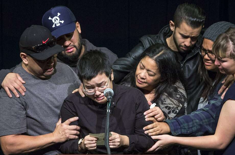 Victoria Plotkin reads from a note she wrote to her sister Vanessa Plotkin, as she is embraced by family and friends on Thursday, Dec. 8, 2016 in Berkeley, Calif. Vanessa, 21, who was Victoria's twin sister, died in the Oakland warehouse fire last week. A vigil was held at Zellerbach Hall for Berkeley undergraduates Jennifer Morris and Vanessa Plotkin, and recently graduated alumni David Cline and Griffin Madden, who all died in an Oakland warehouse fire. 36 people were killed when the fire broke out at the Ghost Ship warehouse on 31st Avenue and International Boulevard in Oakland's Fruitvale neighborhood. Photo: Santiago Mejia, The Chronicle