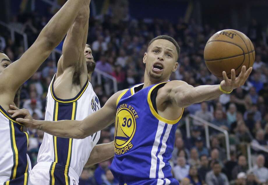 Golden State Warriors guard Stephen Curry (30) reaches for rebound as Utah Jazz center Rudy Gobert, center rear, defends during the second half of an NBA basketball game Wednesday, March 30, 2016, in Salt Lake City. The Warriors won 103-96 in overtime. (AP Photo/Rick Bowmer) Photo: Rick Bowmer, AP
