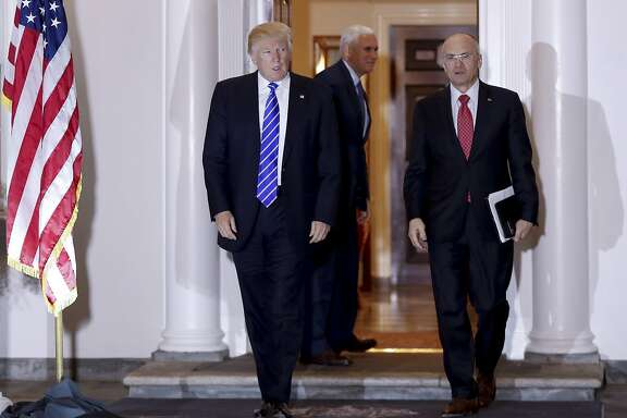 FILE - In this Nov. 19, 2016 file photo, President-elect Donald Trump walks with CKE Restaurants CEO Andy Puzder from Trump National Golf Club Bedminster clubhouse in Bedminster, N.J. Trump is expected to add another wealthy business person and elite donor to his Cabinet, with fast food executive Andrew Puzder as Labor secretary. In the background is Vice President-elect Mike Pence. (AP Photo/Carolyn Kaster)