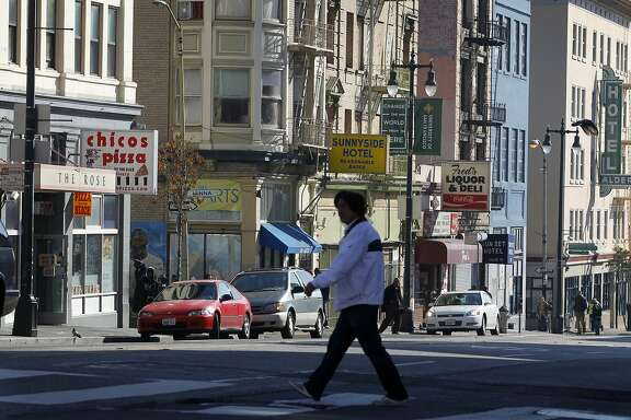 A pedestrian crosses Sixth Street