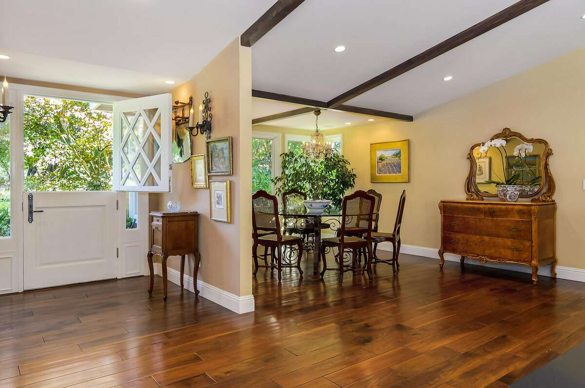A Dutch entry door opens to a foyer set beside a formal dining area.