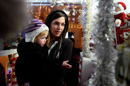 Kate Nelson carries daughter Eve, 2, through a Christmas display on Kansas City Southern's Holiday Express train in Port Arthur on Thursday evening. KCS donates to the Salvation Army at each stop on the annual Christmas tour.  Photo taken Thursday 12/8/16 Ryan Pelham/The Enterprise