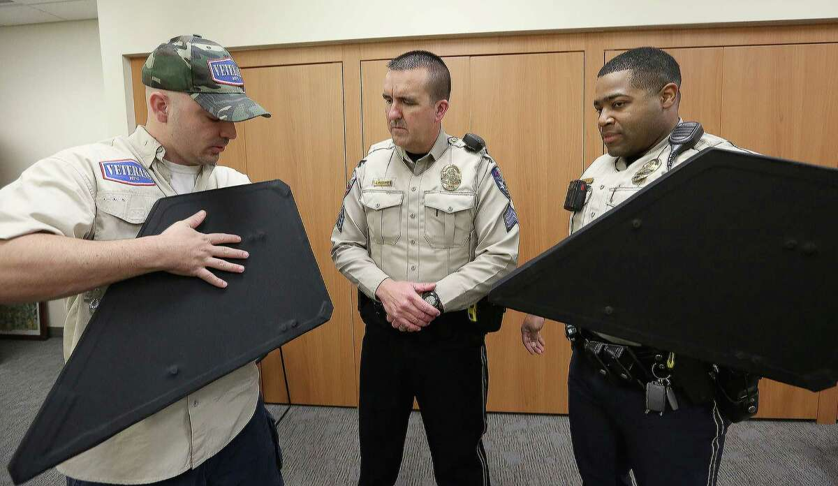 Mike Hlozek, left, co-owner of Katy-based Veterans MFG, demonstrates how to use the newly purchased bulletproof shields to Sgt. John McClure, center, and Officer Jeremy King of the Katy Police Department.