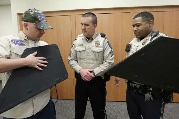 Michael Hlozek, left, co-owner of Katy-based Veterans MFG, demonstrates how to use the newly purchased bulletproof shields to Katy Police Department Sgt. John McClure, left, and Patrol Officer Jeremy King Thursday, Dec. 8, 2016, in Katy. The new bulletproof vests weight about nine pounds and can resist high-velocity armors. ( Yi-Chin Lee / Houston Chronicle )