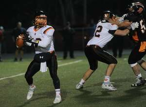 Ridgefield quarterback Drew Fowler looks to pass in the Tigers' 44-41 victory over Shelton in the Class LL state semifinals on Monday. Ridgefield will take on No. 1 Dartien Saturdya afternoon in the championship game at West Haven High.