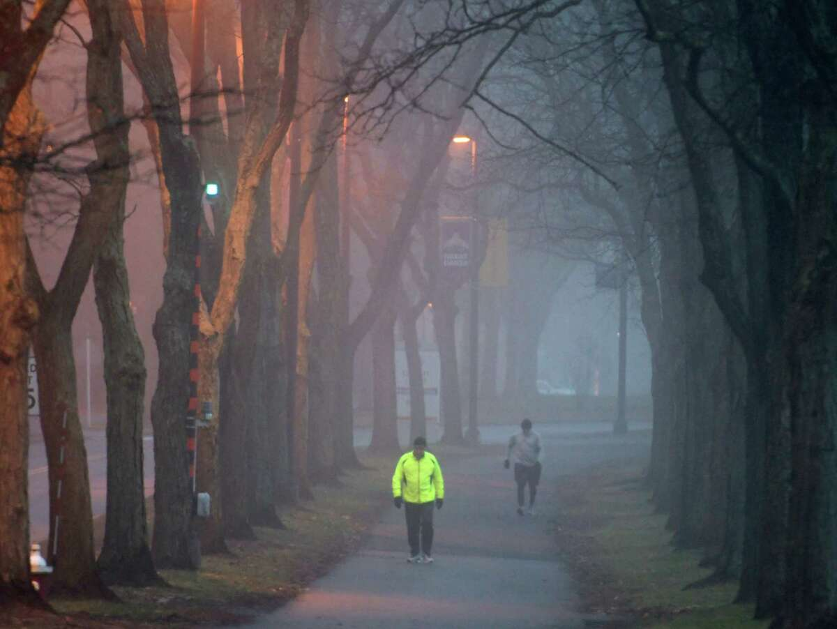 Bill Sprague, left, goes out for his morning walk in the fog at The University at Albany Thursday Dec. 8, 2016 In Albany, N.Y. (Skip Dickstein/Times Union)