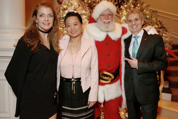 Hostess Paige Fertitta, left, Dr. Lynda Chin and President of MD Anderson Cancer Center Dr. Ronald A. DePinho pose for a photo with Santa at the 11th Annual Santa's Elves to benefit pediatric leukemia and lymphoma research at MD Anderson Cancer Center Children's Cancer Hospital Thursday, Dec. 8, 2016, in Houston.