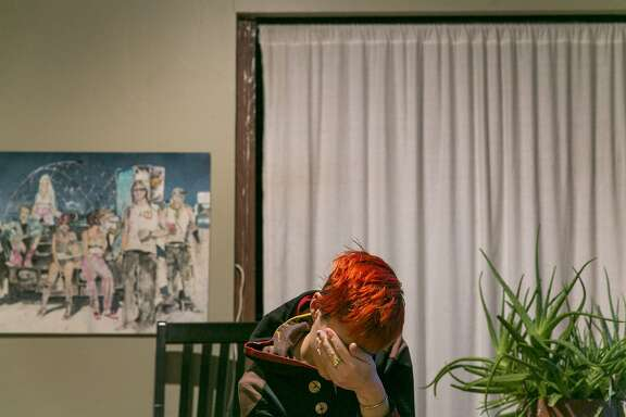 Angela Scrivani takes a moment after calling her mom to chat about her living situation at her live-work space in a shared warehouse on Thursday, Dec. 8, 2016 in Oakland, Calif. The landlord wants to evict Scrivani and other tenents from the warehouse. Scrivani is a painter and photographer. The notice to evict comes days after the Oakland Ghost Ship warehouse fire that killed 36 people.