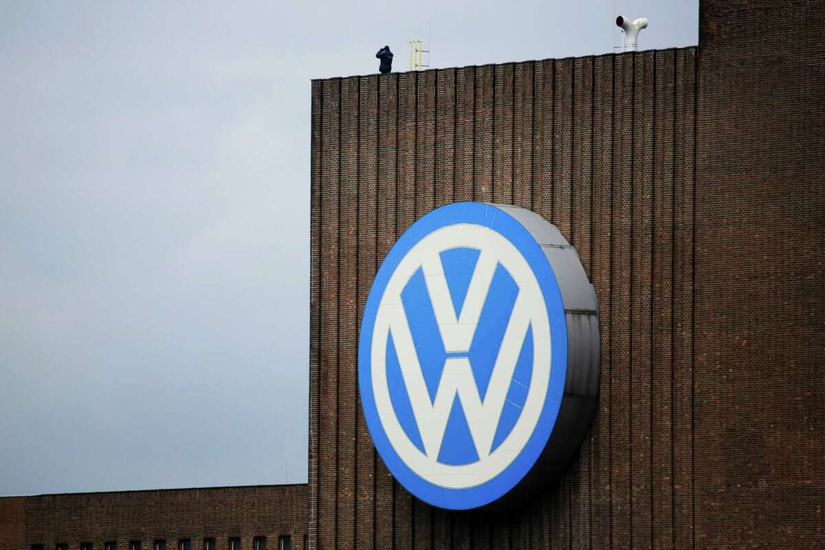FILE - In this April 28, 2016 file picture a security guard stands on the roof of the Volkswagen old power plant and monitors the area during the company's annual press conference in Wolfsburg, Germany.2016. The European Union is starting legal action against Britain, Germany, Spain and Luxembourg for not imposing penalties against Volkswagen for using illegal software to hide vehicle emissions. The European Commission also said Thursday Dec. 8, 2016 that it believes Britain and Germany
