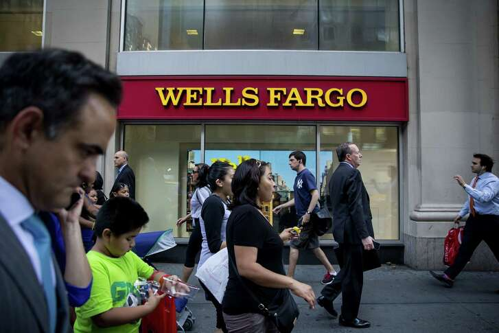"""Pedestrians pass in front of a New York Wells Fargo bank branch. Wells Fargo is continuing its effort to """"address behaviors inconsistent with our vision and values."""""""