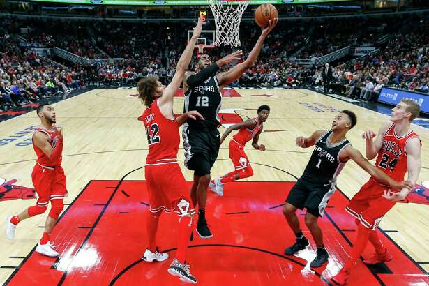 San Antonio Spurs forward LaMarcus Aldridge (12) goes to the basket against Chicago Bulls center Robin Lopez (42) during the first half of an NBA basketball game, Saturday, Oct. 21, 2017, in Chicago. (AP Photo/Kamil Krzaczynski)
