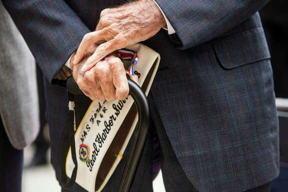 """Pearl Harbor Survivor Aaron Cook, 94, who was stationed on Ford Island, holds his cover as he stands during the playing of """"Taps"""" at a Pearl Harbor remembrance ceremony at the George Bush Presidential Library, Wednesday, Dec. 7, 2016, in College Station, Texas. (Brett Coomer/Houston Chronicle via AP)"""