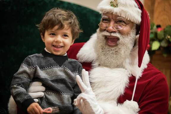 """Larry Jefferson, an Army veteran from Texas, sees himself as """"a messenger to bring hope, love and peace."""" In this Thursday, Dec. 1, 2016 photo, Larry Jefferson, playing the role of Santa, smiles with Jack Kivel, of Prior Lake, for photos at the Santa Experience at Mall of America, in Bloomington, Minn. The nation's largest mall is hosting its first-ever black Santa Claus this this weekend. (Leila Navidi/Star Tribune via AP)"""