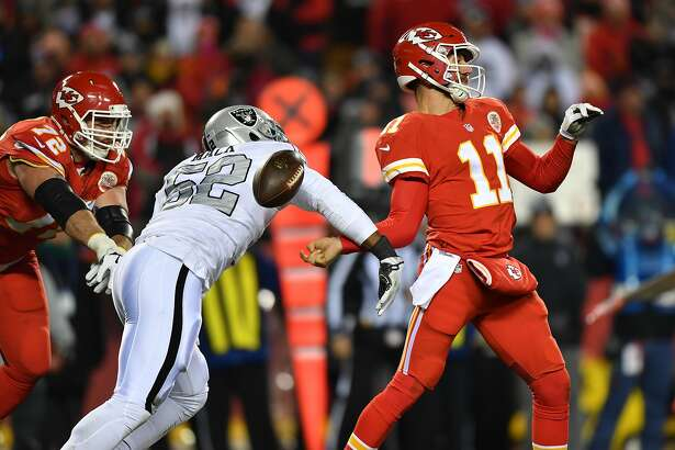 KANSAS CITY, MO - DECEMBER 8: Defensive end Khalil Mack #52 of the Oakland Raiders reaches out to strip the ball from quarterback Alex Smith #11 of the Kansas City Chiefs at Arrowhead Stadium during the third quarter of the game on December 8, 2016 in Kansas City, Missouri. (Photo by Peter Aiken/Getty Images)