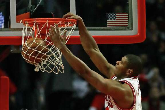 CHICAGO, IL - DECEMBER 08: Cristiano Felicio #6 of the Chicago Bulls dunks over David Lee #10 of the San Antonio Spurs at the United Center on December 8, 2016 in Chicago, Illinois. The Bulls defeated the Spurs 95-91.