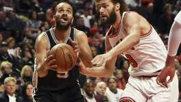 San Antonio Spurs guard Tony Parker (9) is defended by Chicago Bulls center Robin Lopez (8) during the second half of an NBA basketball game in Chicago, Thursday, Dec. 8, 2016. The Bulls won 95-91. (AP Photo/David Banks)