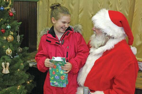 Olivia Woodke  of Port Hope is all giggles as Santa teases her during his annual visit to the Oliver Township Hall in Port Hope. The 10-year-old gave Santa her Christmas wish list while he gave her a bag full of treats.