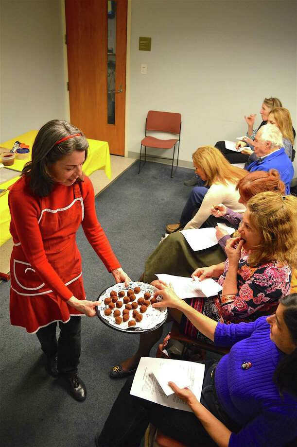 Diane Conroy, chocolate assistant, shares samples with the crowd at a class in making chocolate truffles at the New Canaan Library, Tuesday, Dec. 6, 2016, in New Canaan, Conn. Photo: Jarret Liotta / For Hearst Connecticut Media / New Canaan News Freelance