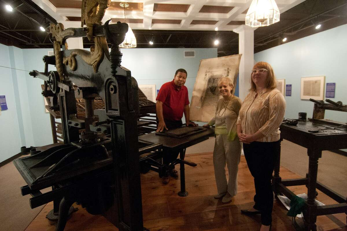 Staff of the Museum of Printing History on West Clay stand with the Museum's 1850s Columbian iron hand press. L-R Charles Criner, Artist-in-Residence; Ann Kasman, Executive Director; Amanda Stevenson, Curator. Photo by R. Clayton McKee