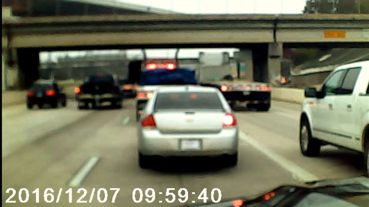 FILE - A screenshot of dashboard camera footage shows two men involved in physical confrontation on Interstate 10 in Houston, Texas on Dec. 12, 2016. Jose Cavazos, the videographer, says the two were driving separate 18-wheelers when the incident began.