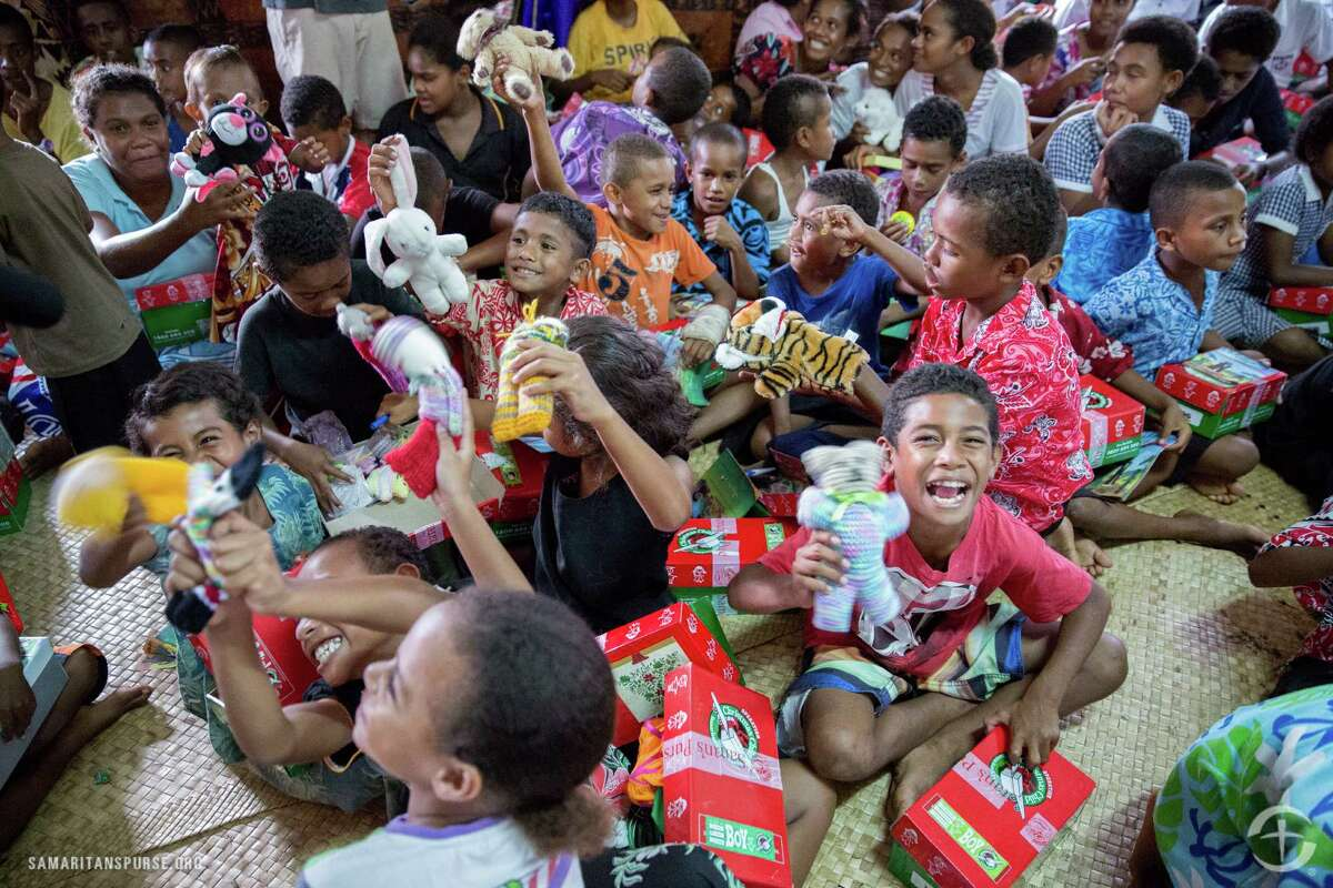 Children in Fiji enjoy opening their gift-filled shoe boxes provided by Operation Christmas Child through Samaritan's Purse.
