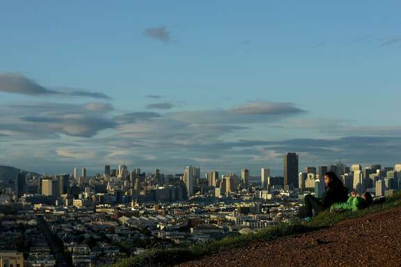 A man and woman are is shown in front of the skyline from Bernal Heights Hill in San Francisco, Wednesday, March 2, 2016. (AP Photo/Jeff Chiu)