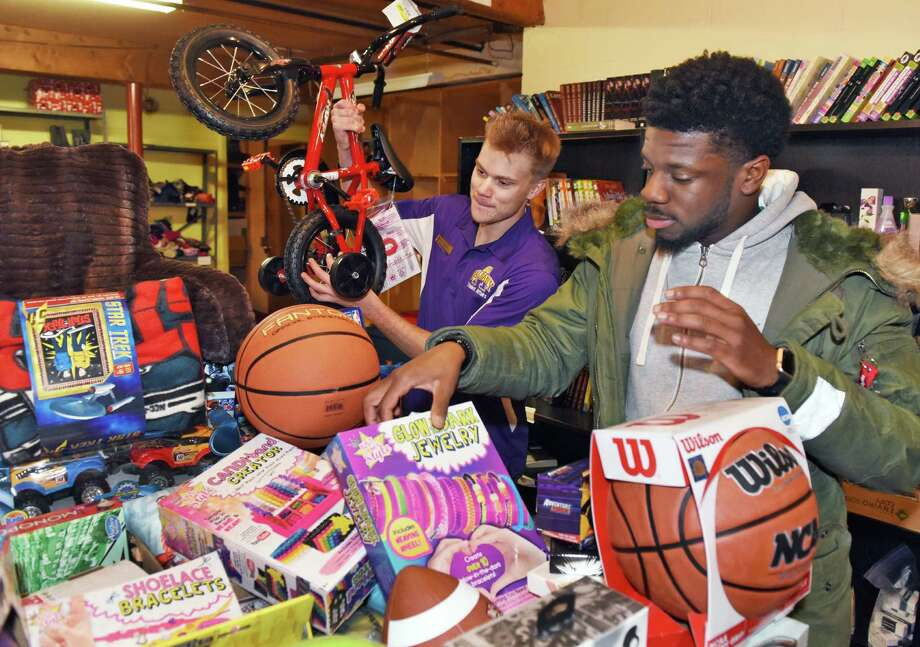 UAlbany grad students Kyle Lockhart, left, and James Brefo stack hundreds of holiday gifts collected for children served by Northern Rivers Family of Services at Parsons Child and Family Center Friday Dec. 9, 2016 in Albany, NY.   (John Carl D'Annibale / Times Union) Photo: John Carl D'Annibale / 20039086A