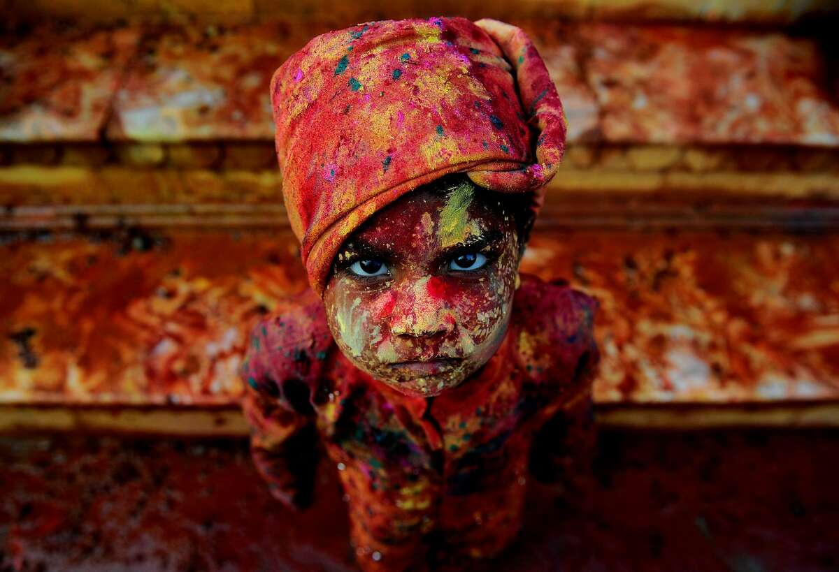An Indian child smeared with coloured powder takes part in the Holi Festival celebrations in Mathura, India on March 18, 2016. Holi, the festival of colours, is a riotous celebration of the coming of spring and falls on the day after full moon annually in March. Revellers spray coloured powder and water on each other with great gusto, whilst adults extend the hand of peace.