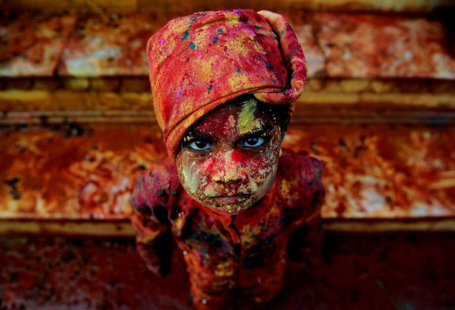 An Indian child smeared with coloured powder takes part in the Holi Festival celebrations in Mathura, India on March 18, 2016. Holi, the festival of colours, is a riotous celebration of the coming of spring and falls on the day after full moon annually in March. Revellers spray coloured powder and water on each other with great gusto, whilst adults extend the hand of peace. Photo: Anadolu Agency/Getty Images