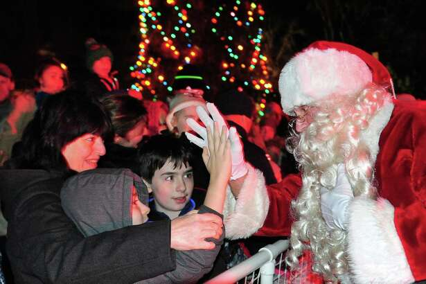 Santa high fives Timothy Preslar, 8, of Fairfield, after the lighting of the Christmas tree on the Town Hall Green in Fairfield on Dec. 2. With Timothy is his mom, Maria, left, and older brother Scott, 12. The festivities began with the Fairfield Woods, Roger Ludlowe and Tomlinson Middle School Chamber Choirs singing songs of the season. The Fairfield Warde Choral Group performed, and the Downtown Theatre Co. rounded out the performances. People in attendance enjoyed some hot chocolate and free glow necklaces, compliments of the Town Youth Council. After the performances, First Selectman Mike Tetreau did the countdown to light the tree at 7 p.m.