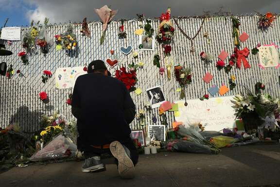 Juan Colmenero prays at a memorial on E. 12th Street in the aftermath of the deadly Ghost Ship warehouse fire in Oakland, Calif., on Tuesday, December 6, 2016.