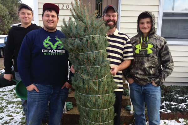 Trevor Traun, Anthony Grifka, Dave Jameson and Travis Stils smile with a tree that was donated by Cook's Tree Sales to be given to a family in need.