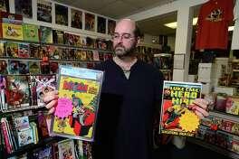 David Kruseski displays rare Batman and Luke Cage comics at his shop, Heroes Comics & Cards, in Norwalk.