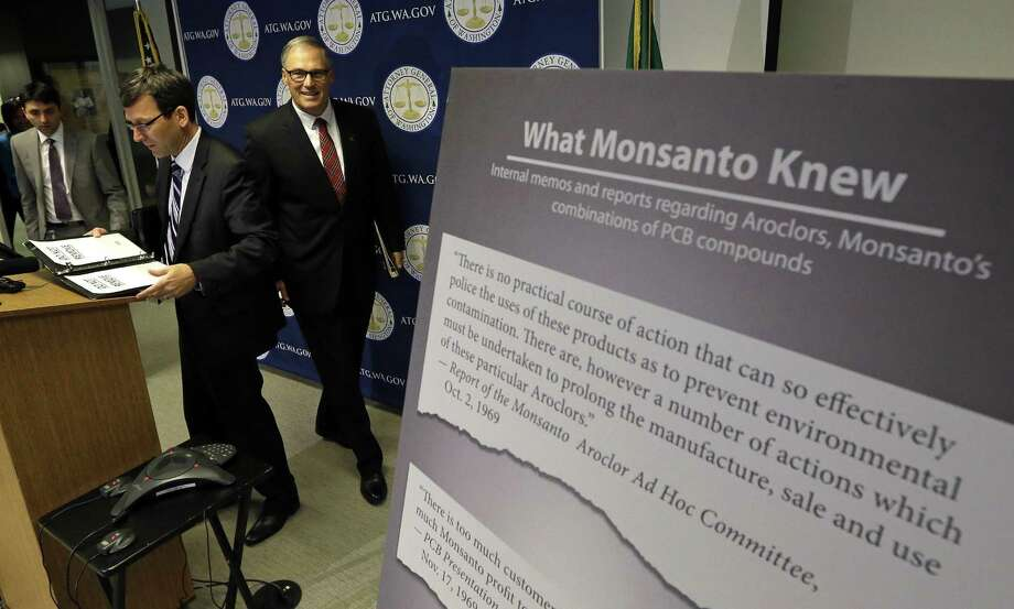 Washington Attorney General Bob Ferguson (left) and Gov. Jay Inslee head into a news conference where Ferguson announced a lawsuit against agrochemical giant Monsanto over pollution from PCBs. Photo: Elaine Thompson /Associated Press / Copyright 2016 The Associated Press. All rights reserved.
