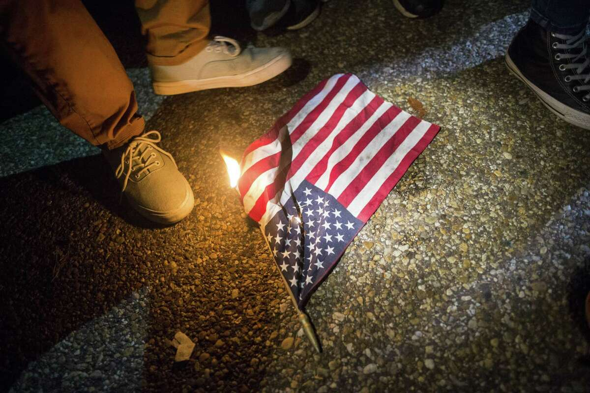 Protesters burn a small American flag outside the White House in Washington in the early morning hours after Election Day. A reader says some of the talk of punishment for flag burning is divisive.