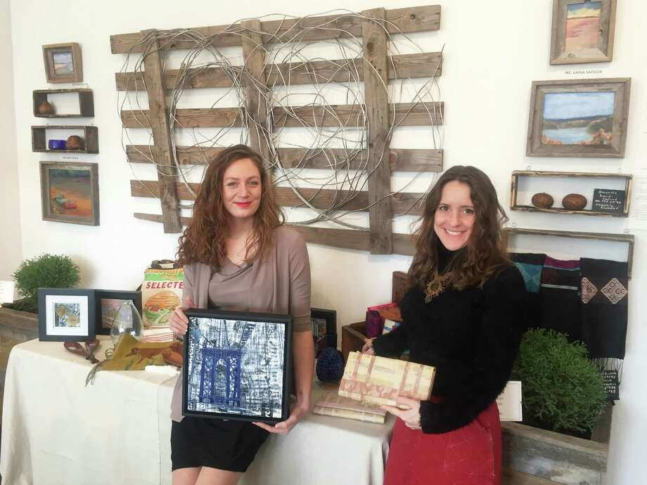 Art and Sound Gallery Curator and Director Audrey Nefores (left), holds sustainable artwork by Natalya Aikens alongside Hands In Founder Susie De Rafelo, who's holding clutches made by a women's empowerment group in Cambodia. Through December and January the gallery is hosting a holiday season market focused on sustainability, where some of the proceeds will go toward charity. Photo: Macaela Bennett / Hearst Connecticut Media