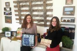 Art and Sound Gallery Curator and Director Audrey Nefores (left), holds sustainable artwork by Natalya Aikens alongside Hands In Founder Susie De Rafelo, who's holding clutches made by a women's empowerment group in Cambodia. Through December and January the gallery is hosting a holiday season market focused on sustainability, where some of the proceeds will go toward charity.