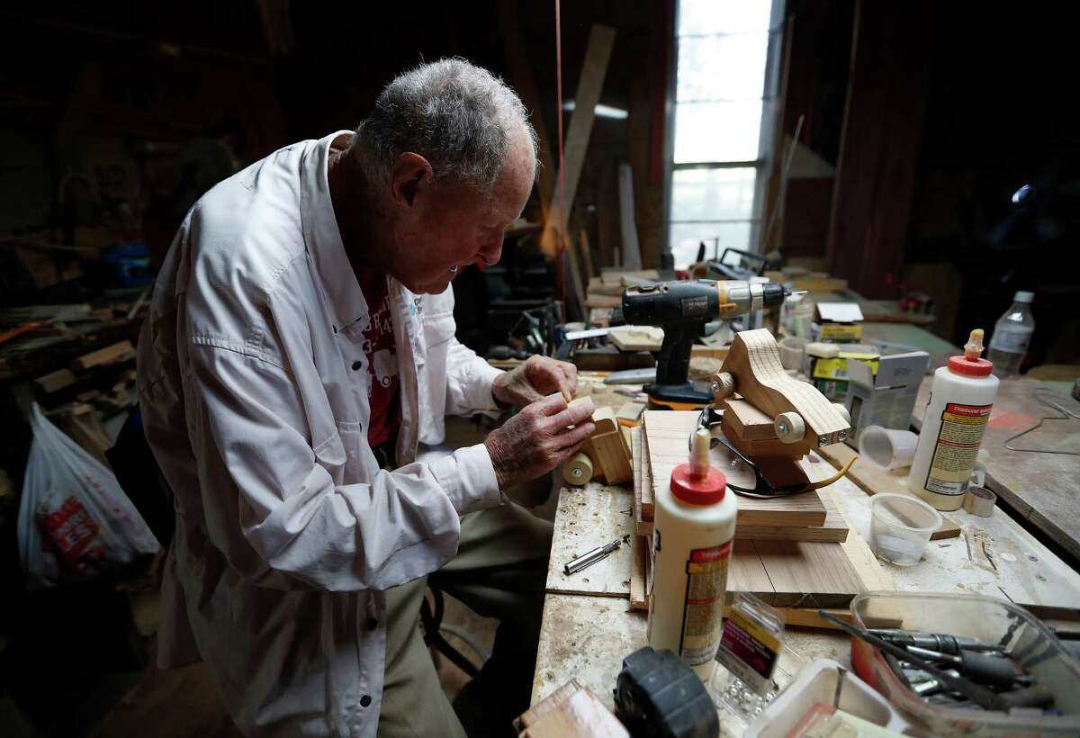 Ernest Raines works on putting the wheels on a tiny wooden car, one of many different kinds of wooden toys that he sells at the local farmer's market, Tuesday,Nov. 15, 2016 in Rosharon. ( Karen Warren / Houston Chronicle )