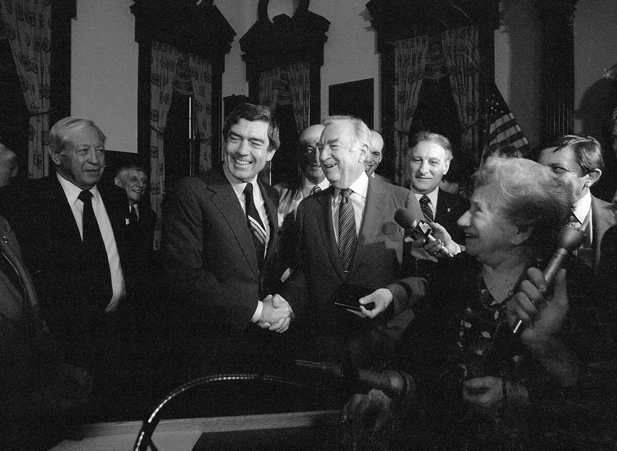 NEW YORK - MARCH 6: The final day of Walter Cronkite as anchor of the CBS Evening News, March 6, 1981. Mr. Cronkite (at right) shakes hands with his replacement as anchor, Dan Rather. CBS founder and president, William S. Paley is at the far left. The event is a ceremony in honor of Mr. Cronkite at New York's city hall. (Photo by CBS via Getty Images)