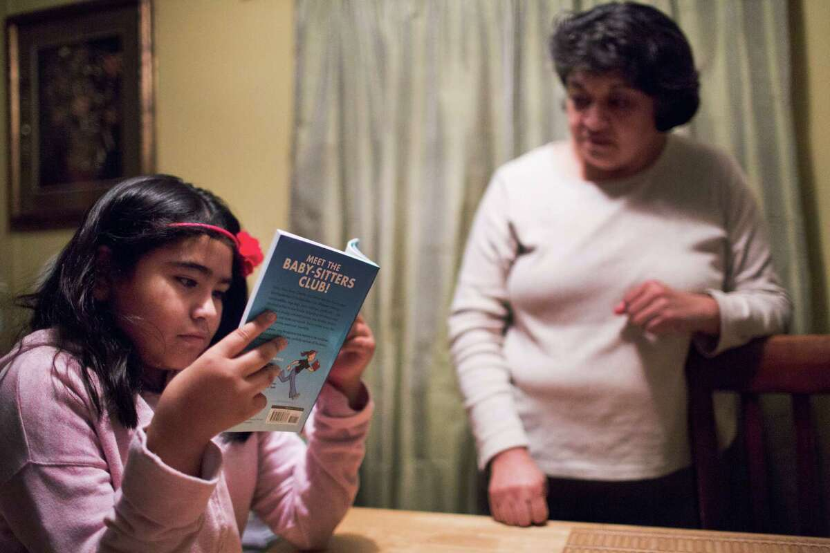 Ashley Rodriguez, 9, tries to read a book as her mother Evangelina Cardenas observes her.Rodriguez is a fourth grader who has always struggled with reading but just recently got placed in special education after years of fighting by her parents.