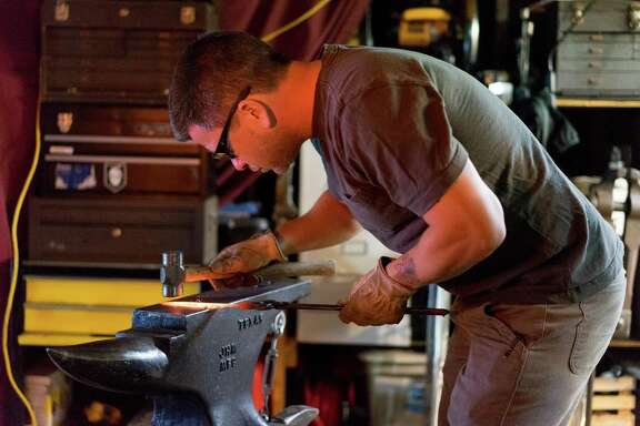 Drew Hash works on a knife in his home in San Francisco.