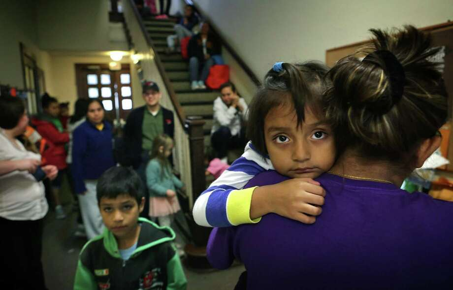 Ashley Rivas, 4, looks over the shoulder of her mother Griselda Rivas, 30, of El Salvador, after arriving at the San Antonio Mennonite Church where hundreds of immigrants from Central America have been dropped off by ICE.  Volunteers mentioned they went out to buy blankets and air mattresses, and the last bus dropped off another group at 3 A.M. on Monday, Dec. 5, 2016. Photo: Bob Owen, Staff / San Antonio Express-News / ©2016 San Antonio Express-News