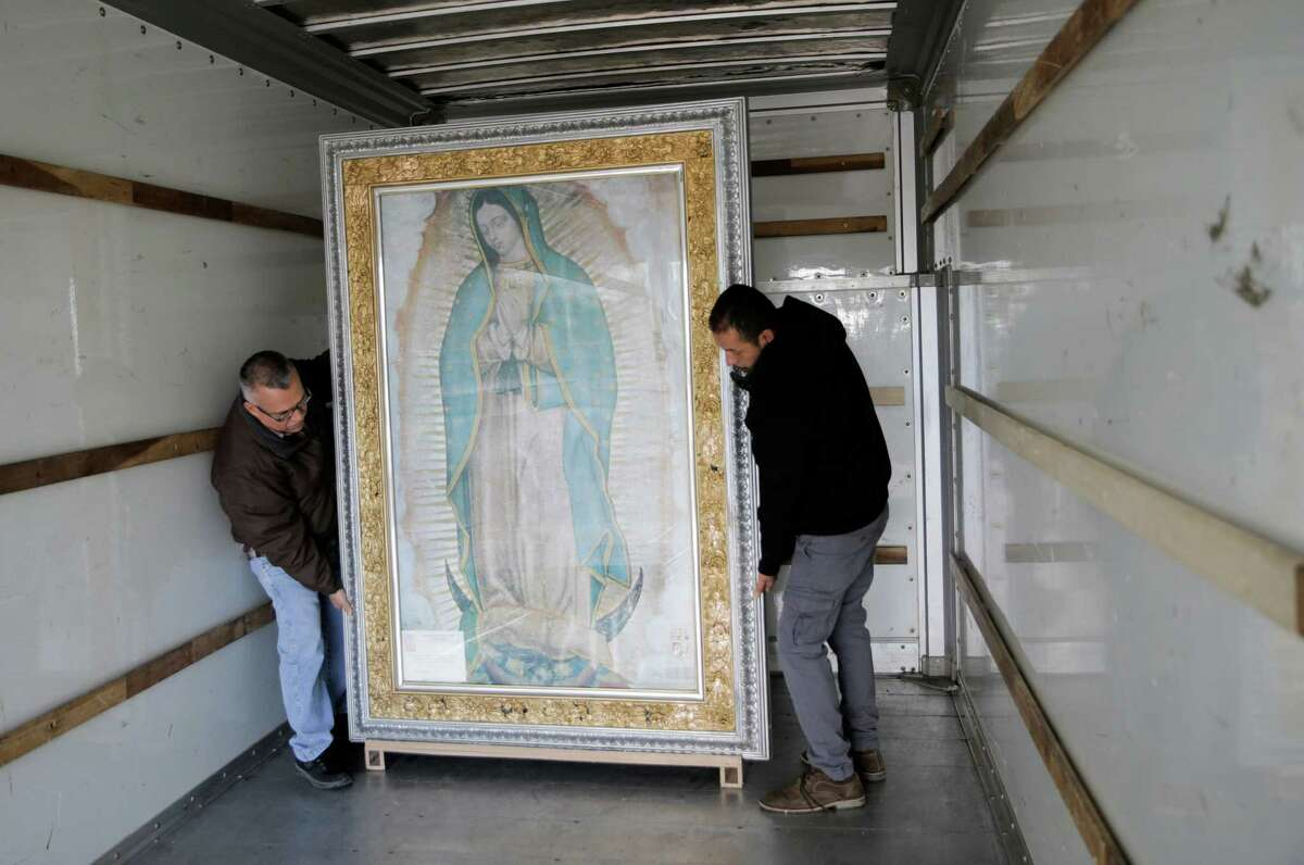 Pablo Guzman,right, president of the Lady of Guadalupe Association in Houston, moves a copy of the painting out of St. Charles Borromeo Catholic Church with help from Roberto Chavez on Friday, Dec. 9, 2016, in Houston. The association has had the painting of Our Lady of Guadalupe since 2008.