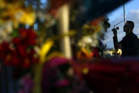 David Sisak places a rose at an E. 12th Street memorial in memory of his friends Johnny Igaz, Amanda Kershaw and Chelsea Dolan in the aftermath of the deadly Ghost Ship warehouse fire in Oakland, Calif., on Tuesday, December 6, 2016. Sisak had a ticket to the December 2nd show at the warehouse but decided to not attend.
