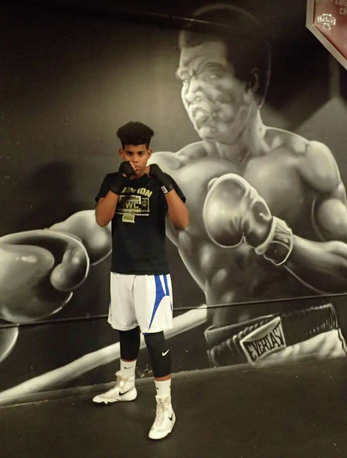 Ali Feliz, a 13-year-old amateur boxer from Danbury takes a break from his training at Champs Boxing Club in Danbury on Dec. 6, 2016. Behind him on the wall is a painting of boxing great Muhammad Ali, after whom Ali, the son of former heavyweight contender Fernely Feliz, is named. Photo: Richard Gregory / Richard Gregory